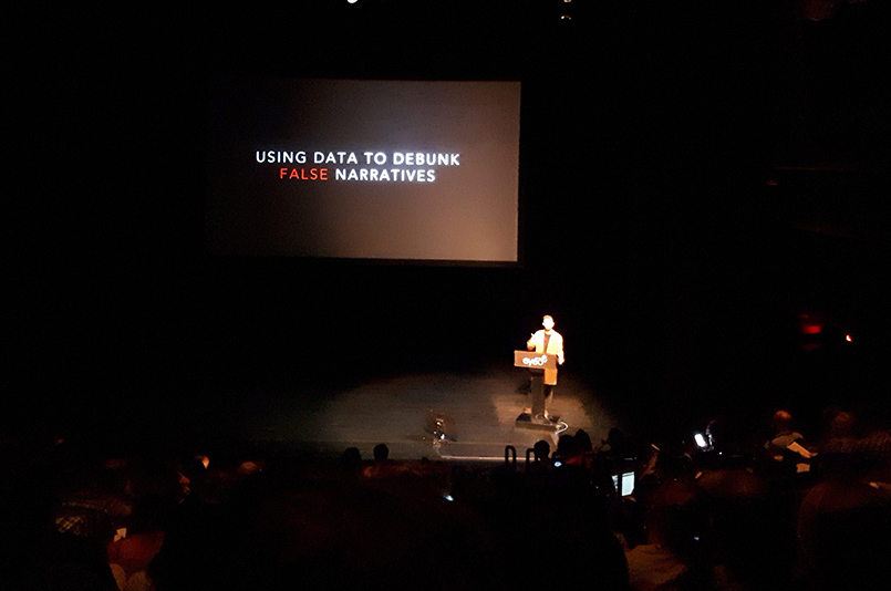 "Photo of the talk by Sam Sinyangwe - the slide reads ""using data to debunk false narratives"""